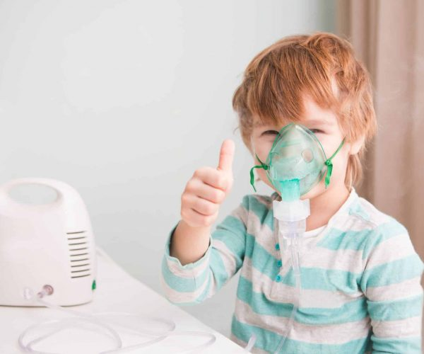 Little boy making inhalation with nebulizer at home.
